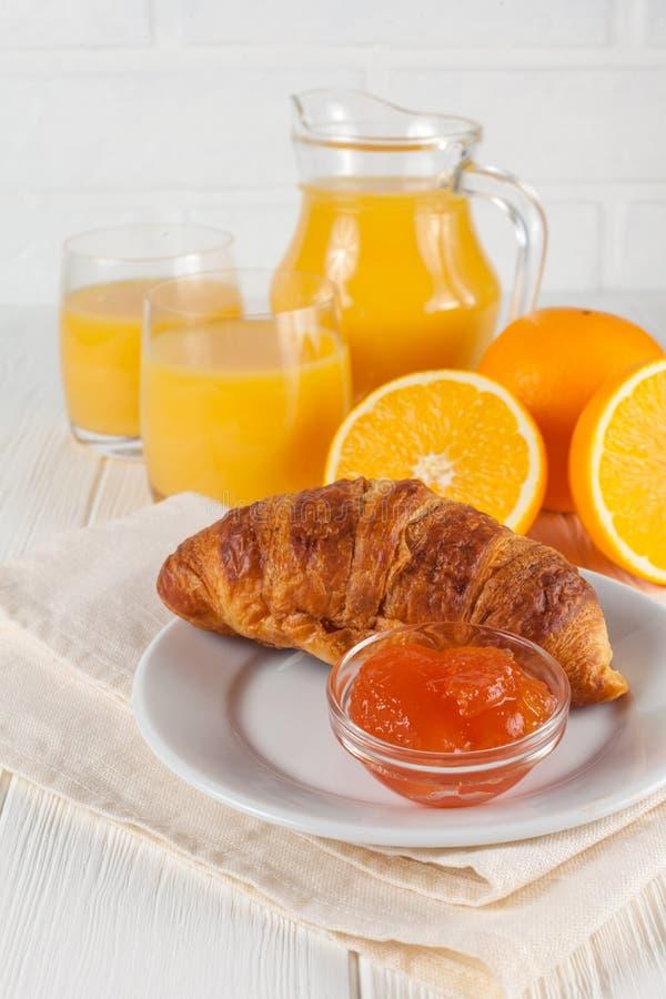 Croissant fraîchement cuit au four, jus d'orange, fruits frais, confiture sur le fond en bois blanc Pâtisseries fraîches de petit photo libre de droits
