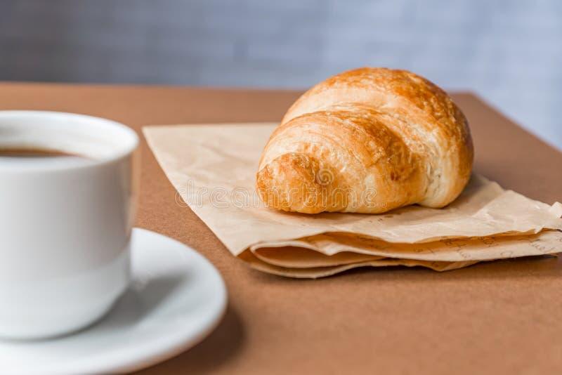 Croissant français de breackfast savoureux servi sur le papier de métier et la tasse de café noir ou d'expresso sur le fond brun  photo libre de droits
