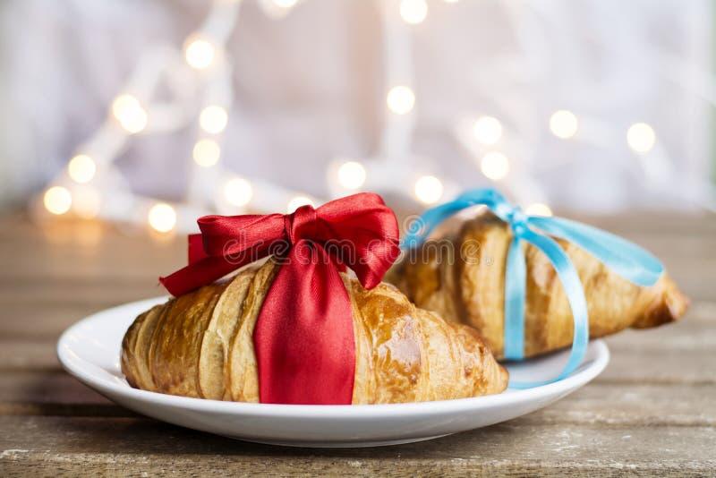 Croissant freschi con il nastro rosso ed il nastro blu su un fondo del bokeh fotografie stock libere da diritti