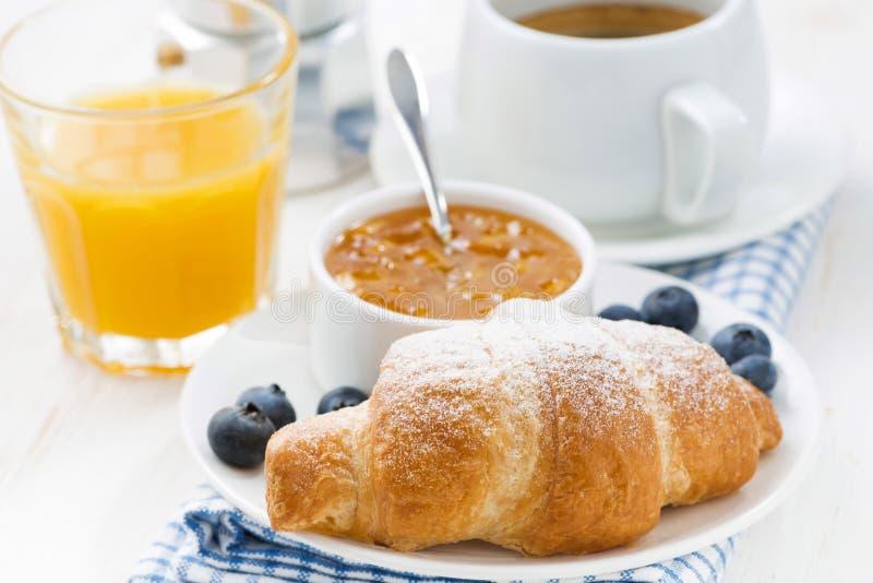 Croissant fresco com doce alaranjado, mirtilos e café fotografia de stock