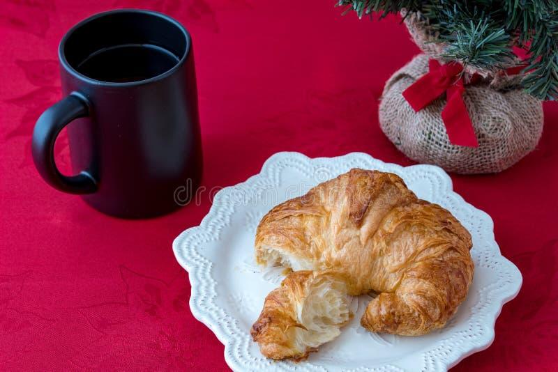 Croissant fresco em uma placa branca da faiança na toalha de mesa vermelha com o copo de café preto imagens de stock royalty free