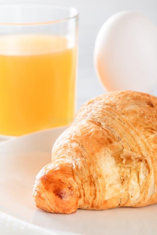 Croissant, gekookt ei en vers gedrukt sap royalty-vrije stock foto