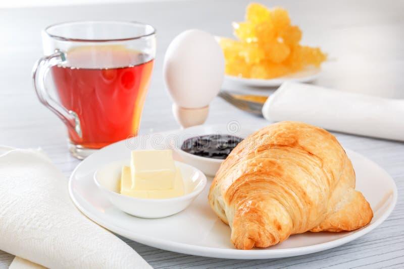 Croissant, gekookt ei, thee, boter, jam Bestek, servet Continentaal Frans Ontbijt royalty-vrije stock foto