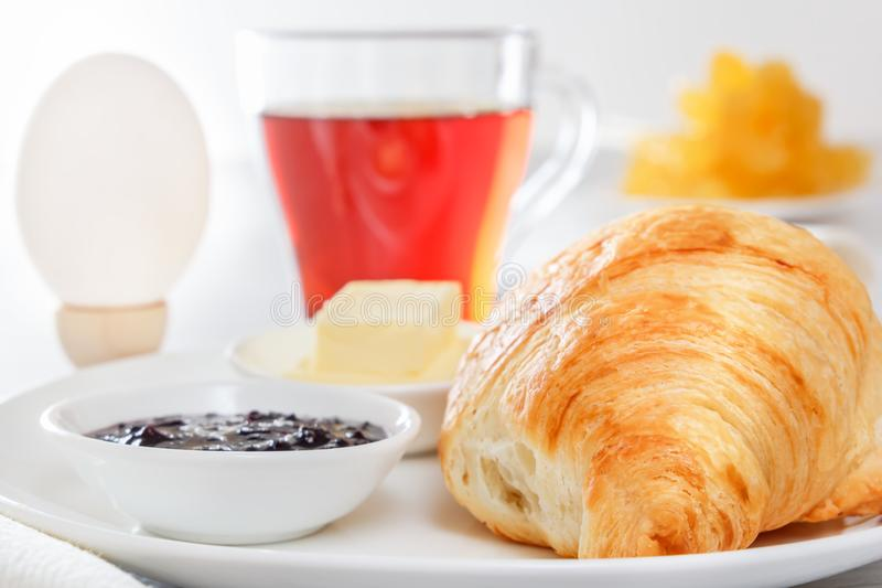 Croissant, gekookt ei, thee, boter, jam Continentaal Frans Ontbijt stock fotografie
