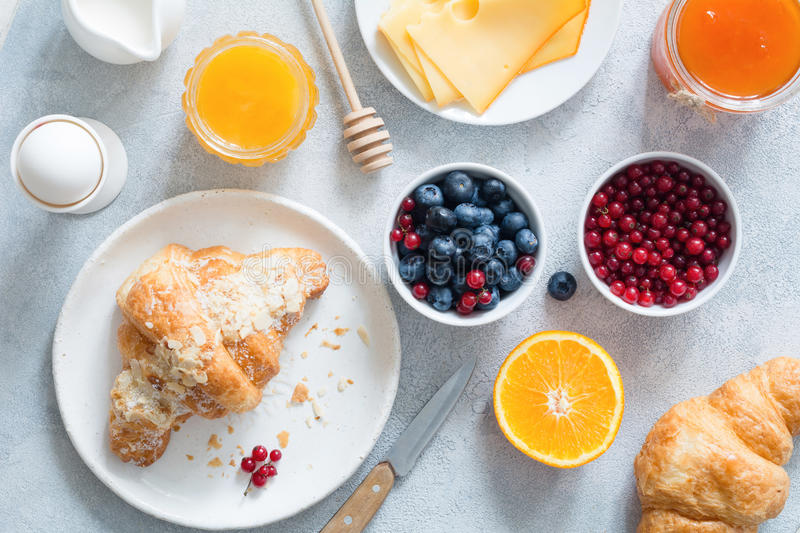 Croissant, honey, cheese, jam, fresh berries and fruits. Continental breakfast stock image