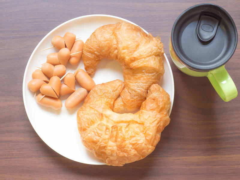 Croissant i serca kiełbasa z filiżanką na drewnianym stole obraz stock