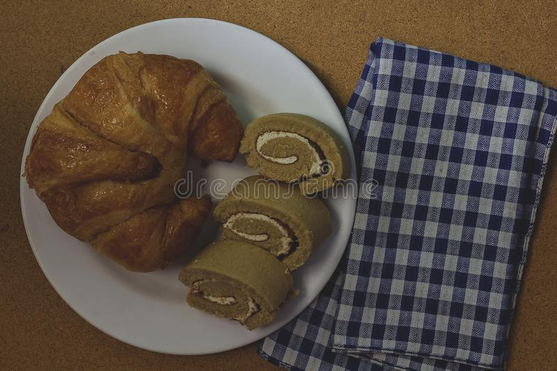 Croissant with jam roll on white plate. Croissant with jam roll on a white plate is a treat for dessert stock images