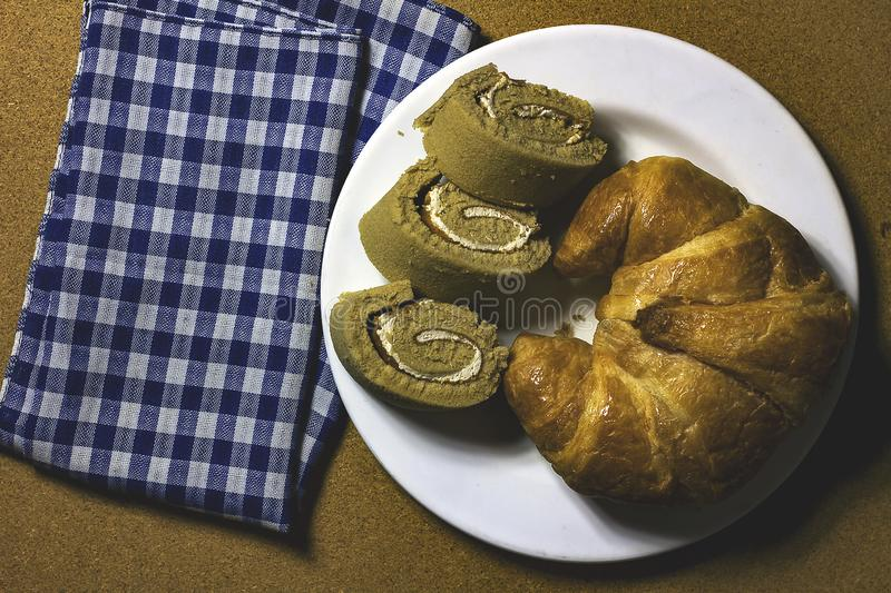 Croissant with jam roll on white plate. Croissant with jam roll on a white plate is a treat for dessert stock photo