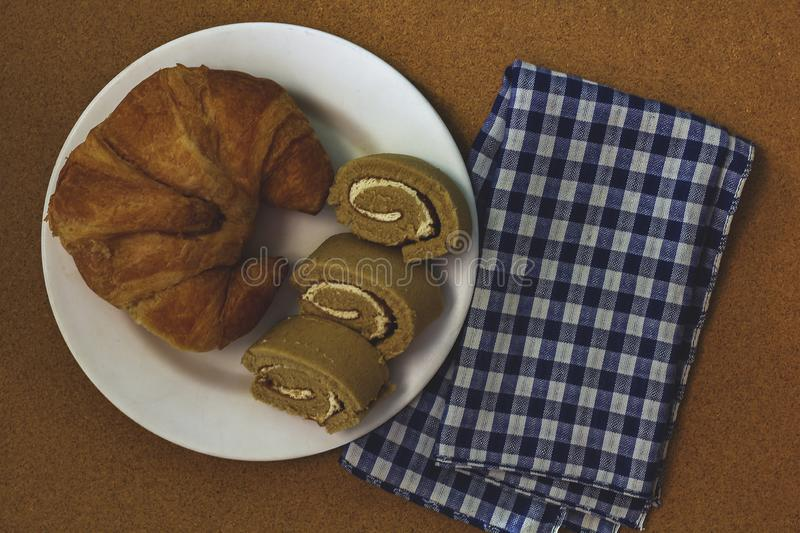 Croissant with jam roll on white plate. Croissant with jam roll on a white plate is a treat for dessert royalty free stock photography