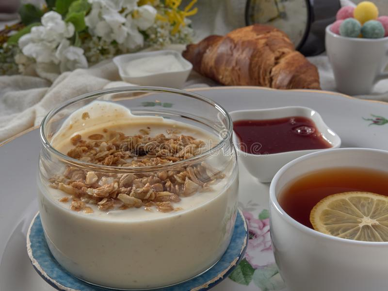 Croissant,jam ,tea with lemon, on a porcelain dish. Yogurt with muesli and strawberry jam royalty free stock images