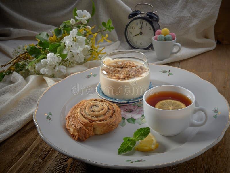 Croissant,jam ,tea with lemon, on a porcelain dish. Yogurt with muesli and strawberry jam stock image