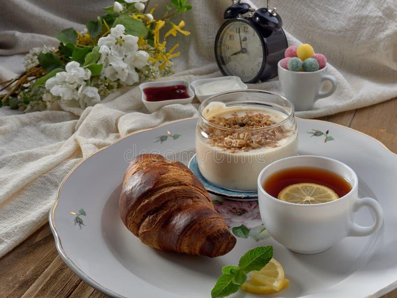 Croissant,jam ,tea with lemon, on a porcelain dish. Yogurt with muesli and strawberry jam royalty free stock photography