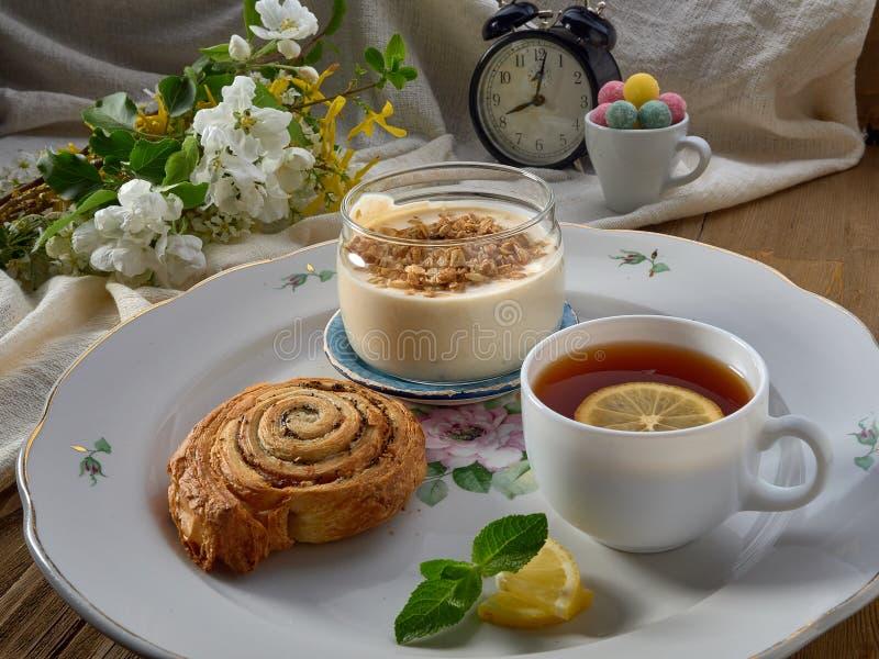 Croissant,jam ,tea with lemon, on a porcelain dish. Yogurt with muesli and strawberry jam stock photo