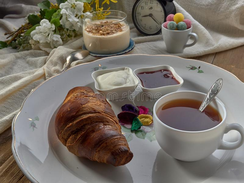 Croissant,jam ,tea with lemon, on a porcelain dish. Yogurt with muesli and strawberry jam royalty free stock image