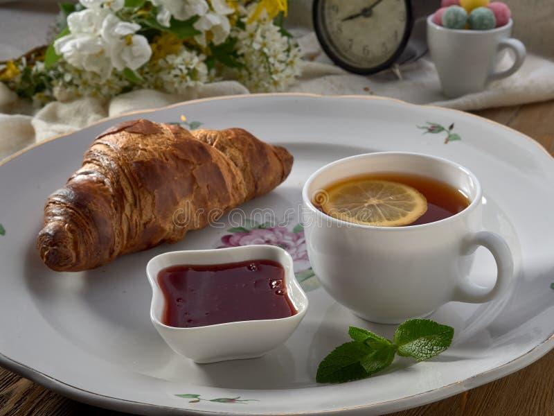 Croissant,jam ,tea with lemon, on a porcelain dish. Yogurt with muesli and strawberry jam stock images