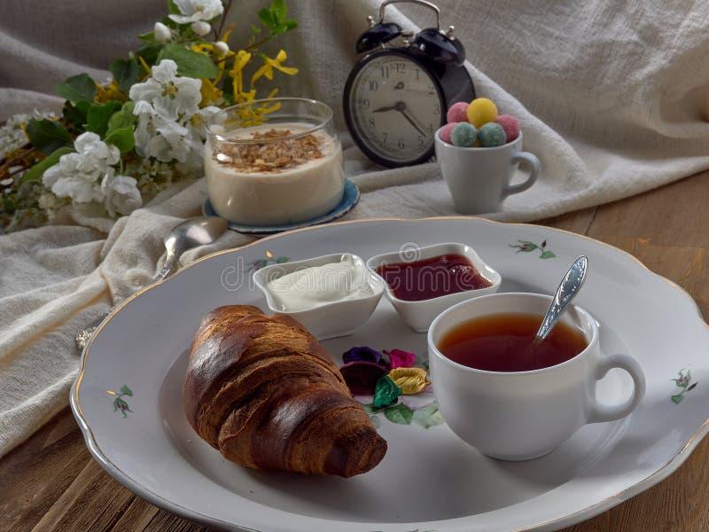 Croissant,jam ,tea with lemon, on a porcelain dish. Yogurt with muesli and strawberry jam royalty free stock photo