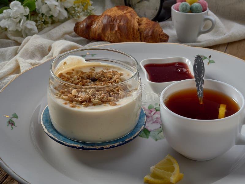 Croissant,jam ,tea with lemon, on a porcelain dish. Yogurt with muesli and strawberry jam royalty free stock photos