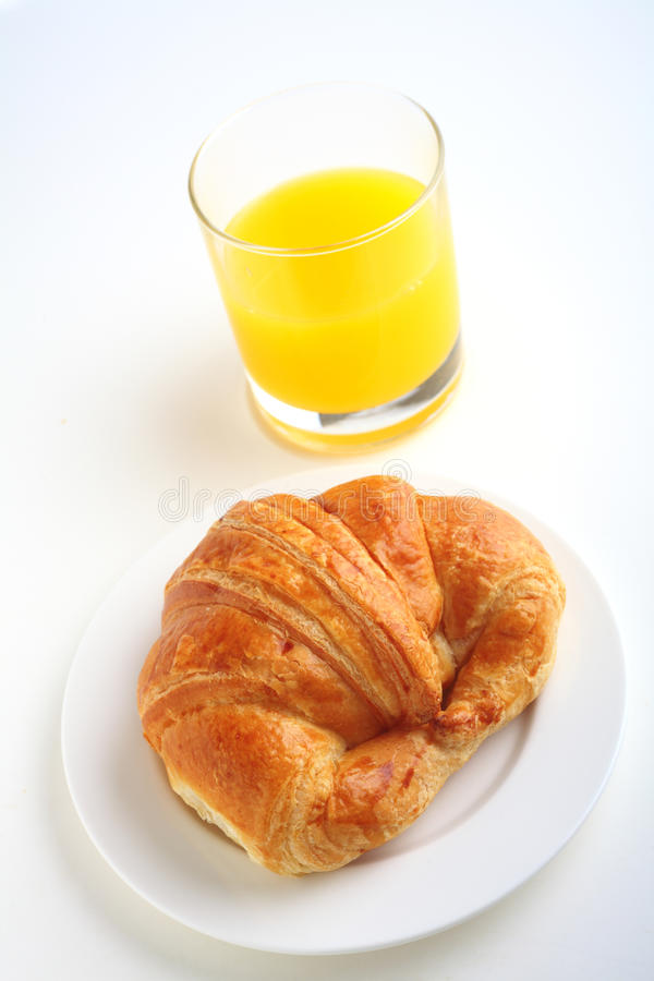 Croissant and juice vertical royalty free stock photo
