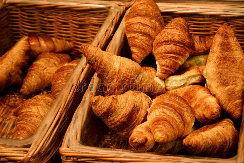 Croissant marrons dourados inchado nas cestas de vime das vendas, cozidas recentemente, com iluminação natural imagens de stock royalty free