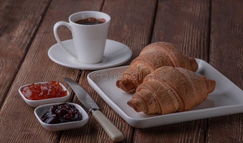 Croissant met koffie en jam van kers en abrikoos wordt gemaakt die royalty-vrije stock afbeelding