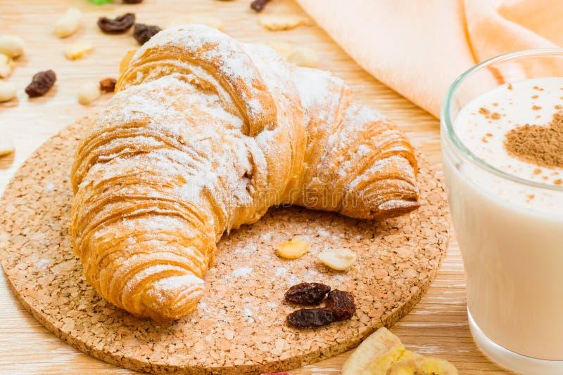 Croissant no açúcar pulverizado e no vidro do leite com coração da canela fotografia de stock royalty free