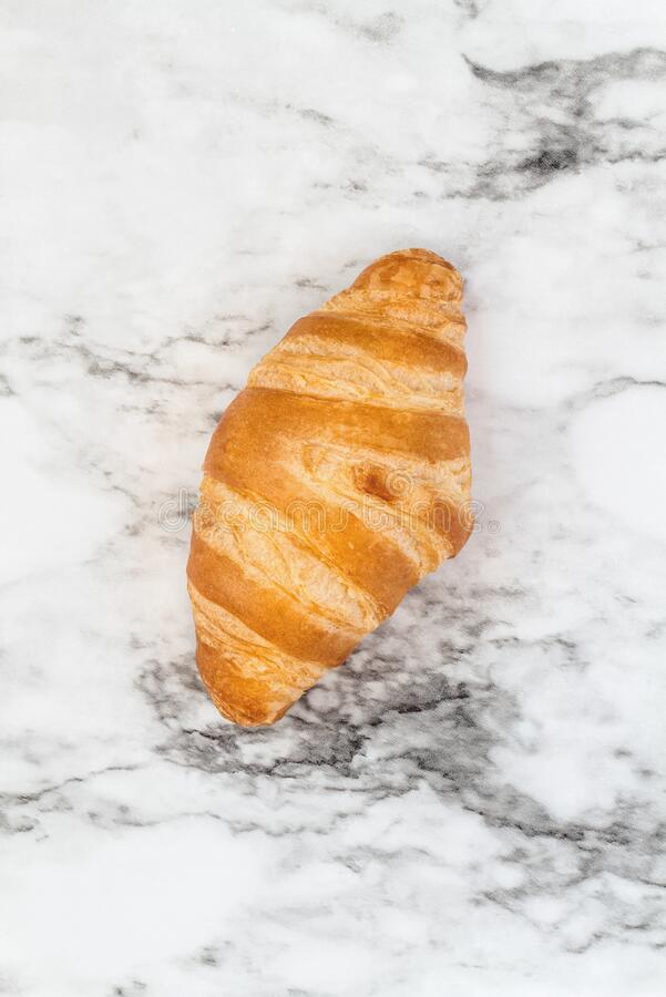Croissant over a Marble Background. One fresh homemade croissant or crescent rolls over marble background  Image shot from top view royalty free stock photography