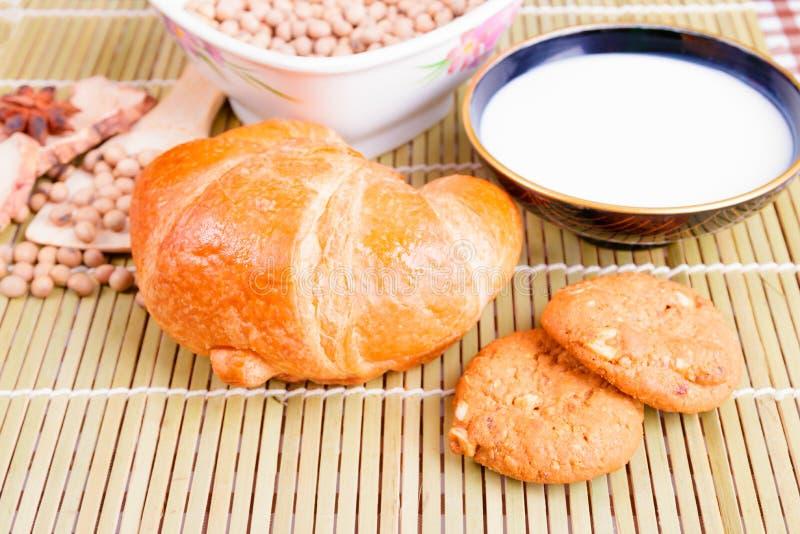 Croissant piec chleb z mlekiem w puchar soj fasoli w filiżanek pikantność na drewnianym bambusie i ciastku zdjęcia royalty free