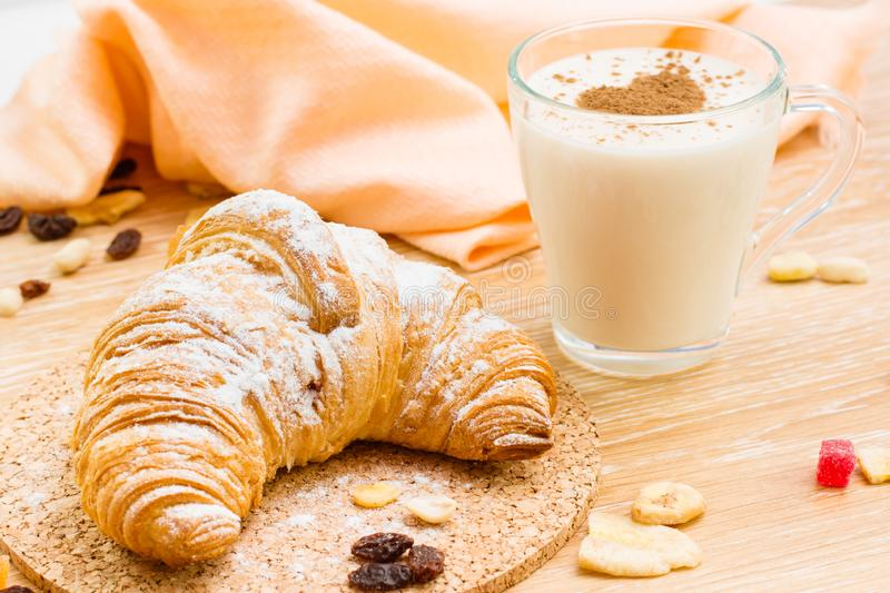 Croissant in powdered sugar and glass of milk wiht heart from cinnamon. On a wooden table stock image