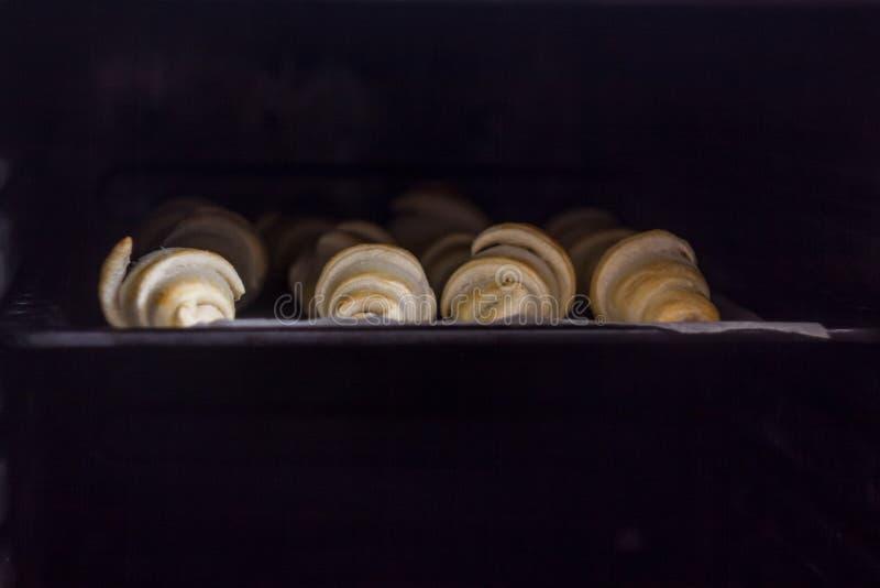 Croissant recentemente cozidos com chocolate em uma bandeja de cozimento no forno fotografia de stock royalty free