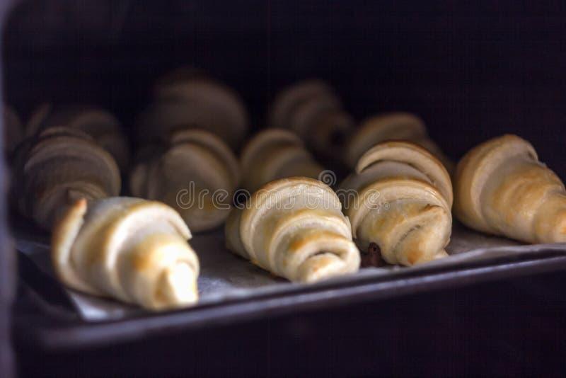 Croissant recentemente cozidos com chocolate em uma bandeja de cozimento no forno imagens de stock