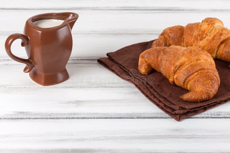 Croissant recentemente cozidos no guardanapo marrom, creme no jarro de leite cerâmico no fundo de madeira velho branco Pastelaria fotografia de stock