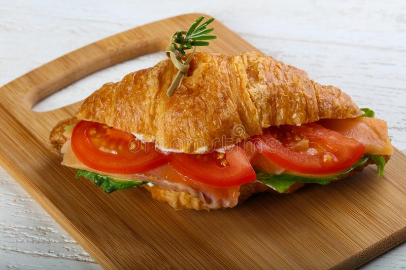 Croissant with salmon. Served rosemary on wood background royalty free stock image