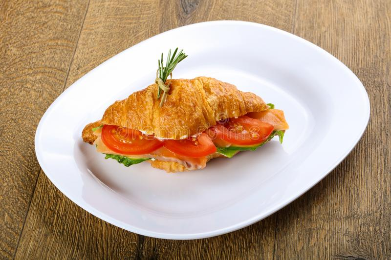Croissant with salmon. Served rosemary on wood background stock photo
