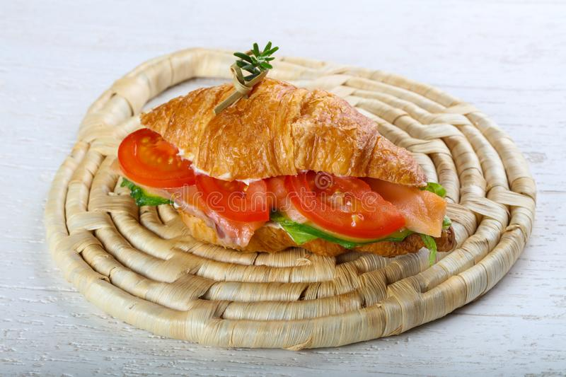 Croissant with salmon. Served rosemary on wood background stock photography