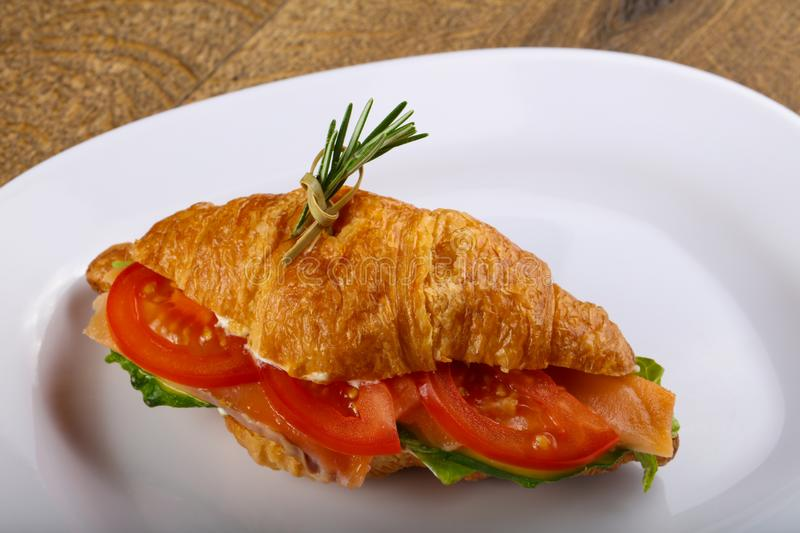 Croissant with salmon. Served rosemary on wood background stock photos