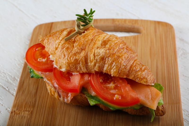 Croissant with salmon. Served rosemary on wood background royalty free stock images