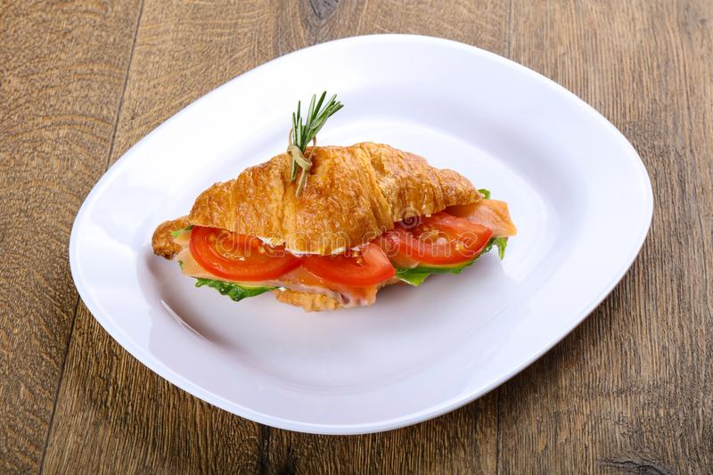 Croissant with salmon. Served rosemary on wood background stock images