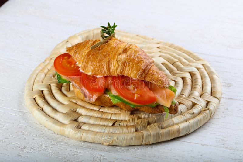 Croissant with salmon. Served rosemary on wood background royalty free stock photos