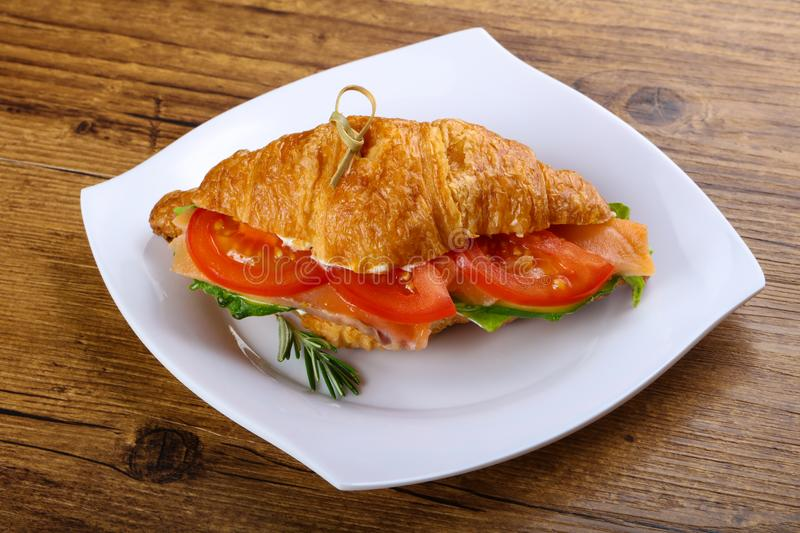 Croissant with salmon. Served rosemary on wood background royalty free stock photo