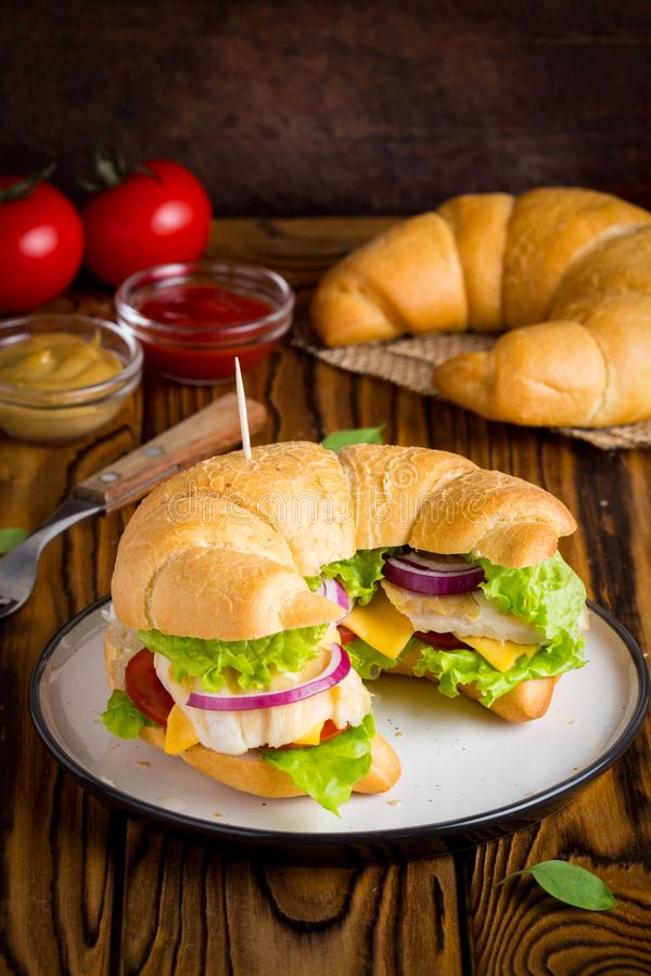 Croissant sandwich with chicken, vegetables, cheese, tomato, oni royalty free stock photo