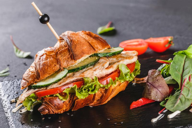 Croissant sandwich with fillet grilled chicken, fresh vegetables, cheese and greens on black shale board over black stone. Background. Healthy food concept royalty free stock photo