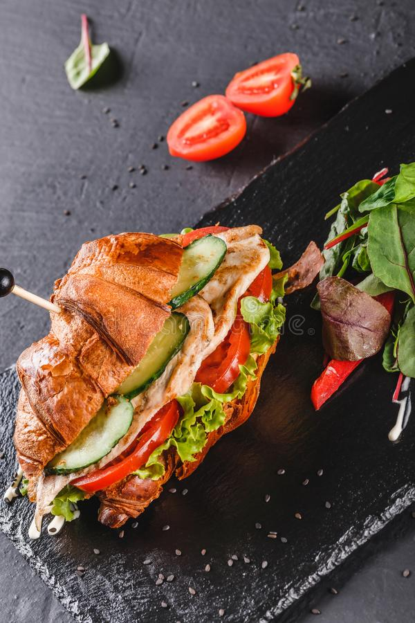 Croissant sandwich with fillet grilled chicken, fresh vegetables, cheese and greens on black shale board over black stone. Background. Healthy food concept stock photo