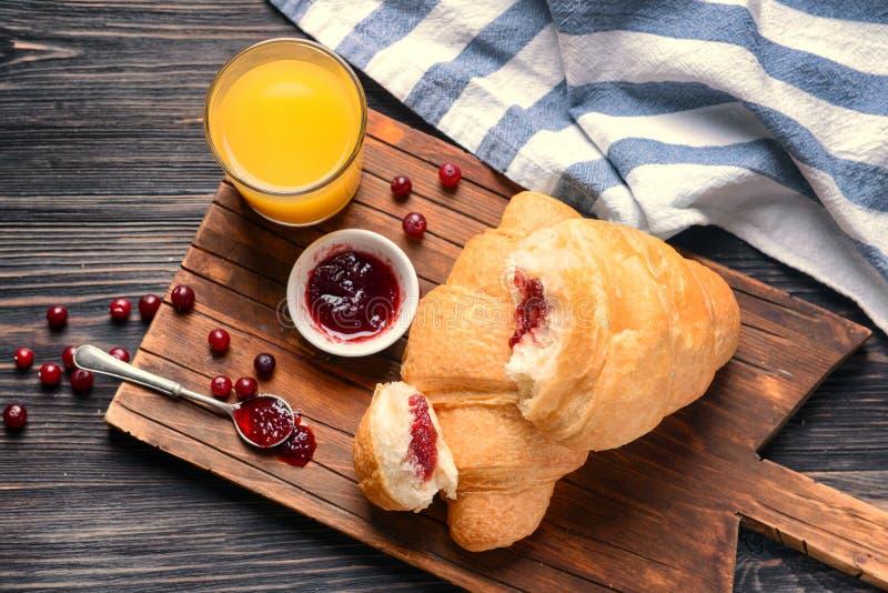 Croissant saporiti con inceppamento e vetro deliziosi di succo d'arancia sul bordo di legno immagine stock