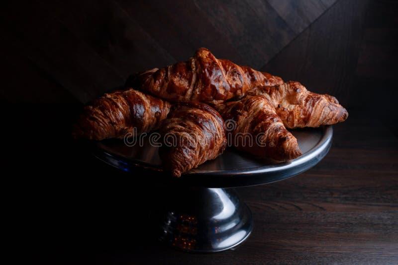 Croissant saporiti dorati freschi con cioccolato su un vassoio elegante su una tavola d'annata in un ristorante Prima colazione d immagine stock