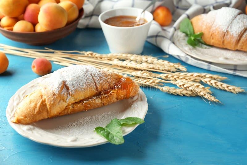 Croissant savoureux avec de la confiture délicieuse d'abricot du plat photographie stock
