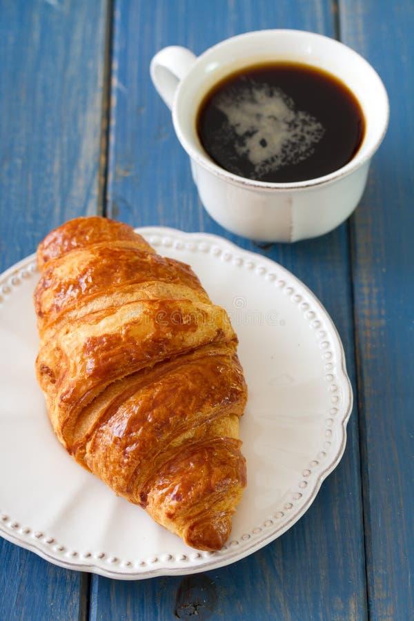Croissant in schotel met koffie stock foto's