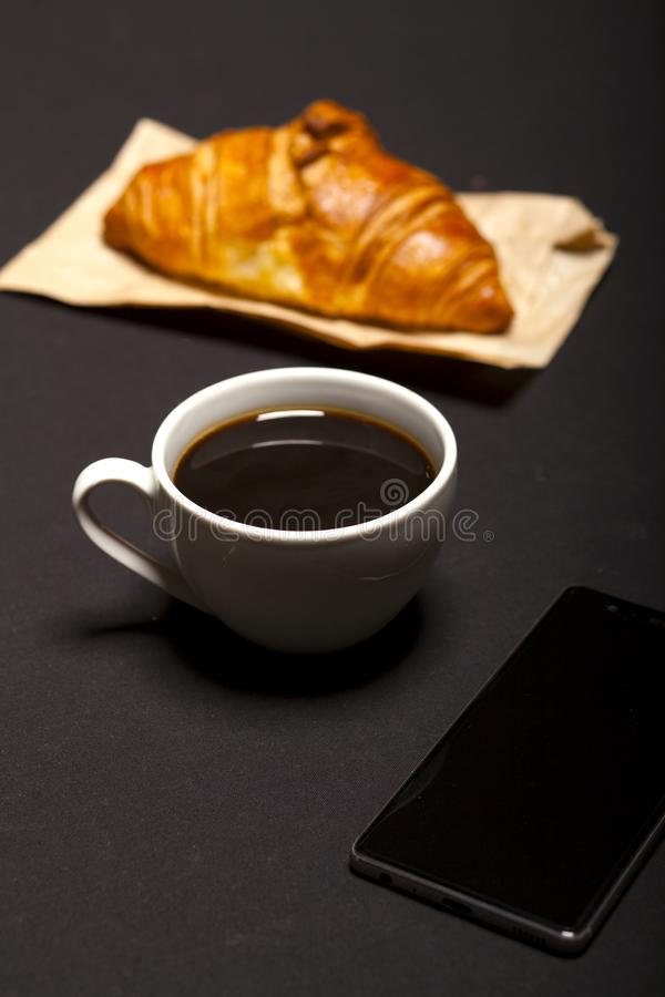 Croissant, smartphone and cup of coffee on black background royalty free stock image