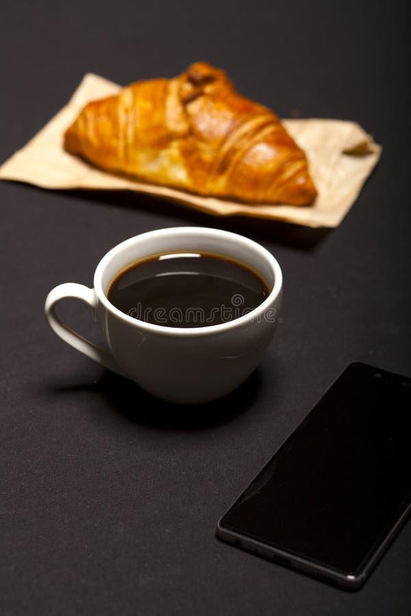 Croissant, smartphone e tazza di caffè su fondo nero immagine stock libera da diritti