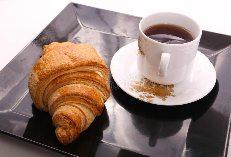 Croissant with tea. On black Tray stock image