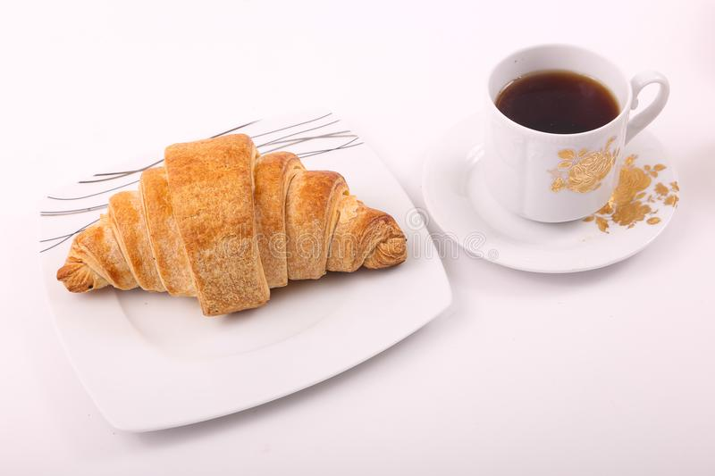 Croissant with tea. On white plate stock photo